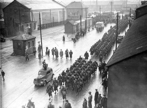 The first troops of the United States expeditionery force to Europe arrive in Belfast. The troops disembarked at the Spencer Basin and the photograph shows a detachment marching along Duncrue Street. 26/1/1942.