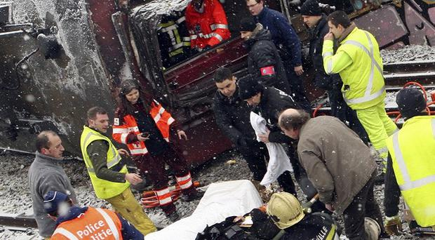 Rescue workers help an injured passenger after a train crash near Brussels, Belgium (AP)
