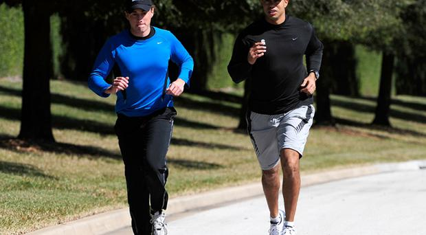 Tiger Woods (R) jogs with an unidentified friend near his home on February 17, 2010 in Orlando, Florida