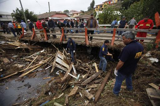 Police officers search for victims after an earthquake in Curanipe, some 389 km., about 241 miles, southwest Santiago, Sunday, Feb. 28
