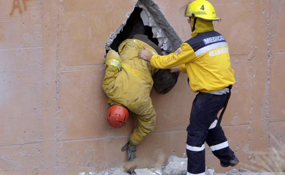 Rescue workers looks for earthquake victim in a collapsed building in Concepcion, Chile, Sunday, Feb. 28, 2010.