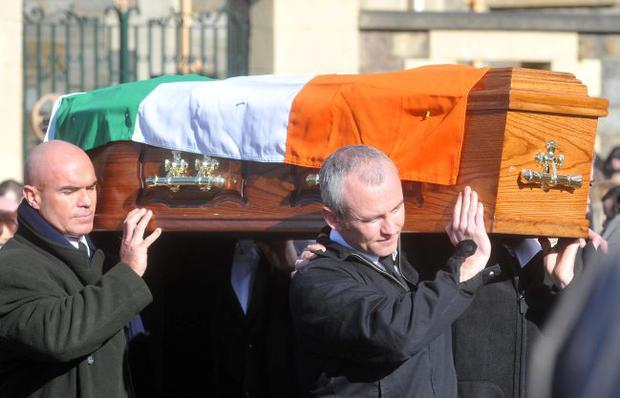 The father of Ciaran Doherty, 'left, carries his son's coffin during his funeral at Long tower chapel in Derry
