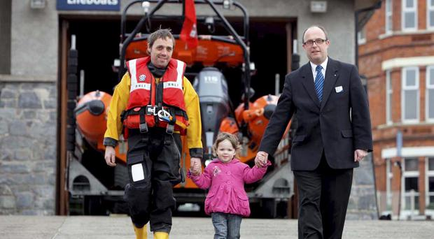 NO FEE©Press Eye Ltd Northern Ireland 14th March 2010Mandatory Credit - Photo- Brian Thompson/ Presseye.comRNLI lifeboat crewmember Ewan Rathbone-Scott and David Johnston, Translink NI Railways Line Supervisor, Bangor take a stroll with two year old Natasha Wright outside their local lifeboat station to support the Holywood to Bangor sponsored coastal walk on Sunday 11 April in aid of Bangor RNLI. Translink NI Railway is providing courtesy rail travel along the route to participants.
