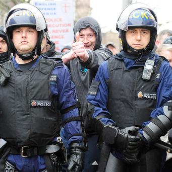 A supporter of the English Defence League gestures behind the police line in Bolton