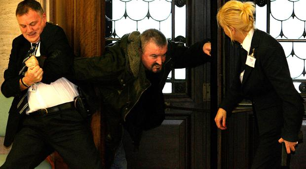 Loyalist murderer Michael Stone pictured being restrained during the 2006 attack at Stormont