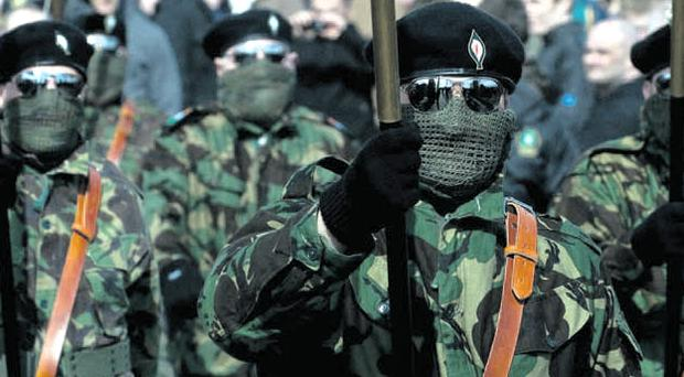 Sinister: Masked flag bearers lead the 32 County Sovereignty Movement Easter Rising parade in Derry