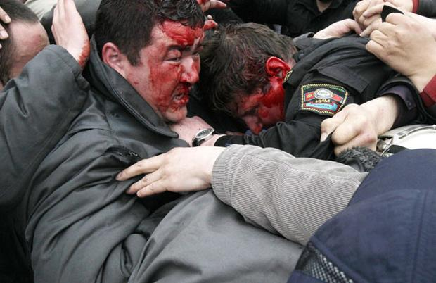 Blooded Kyrgyz police officers huddle together for protection, as they are attacked by protestors in Bishkek, Kyrgyzstan