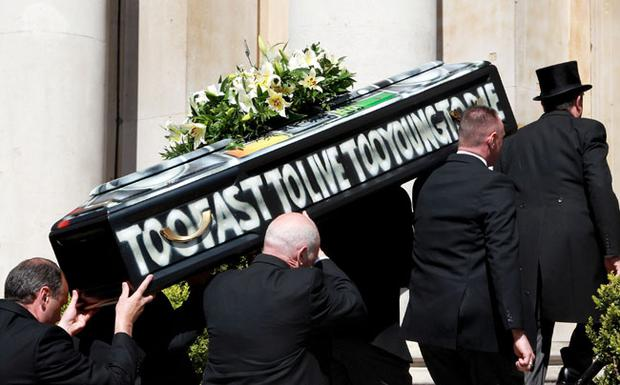 Malcom McLaren's coffin is carried into church at his funeral in North London