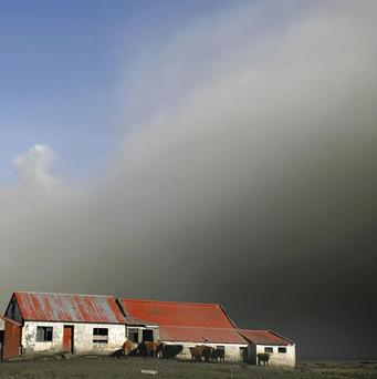 A plume of ash from the volcano under the Eyjafjallajokull glacier covers a farm in Thorvaldseyri, Iceland