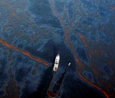 A boat works to collect oil that has leaked from the Deepwater Horizon wellhead in the Gulf of Mexico