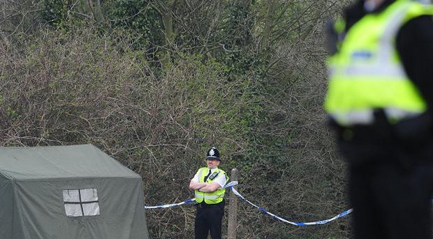 Police stand guard at the site where two brothers, who are challenging their sentences, sadistically tortured a pair of young boys