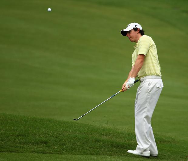 Rory McIlroy of Northern Ireland chips to the 11th green during the first round of THE PLAYERS Championship
