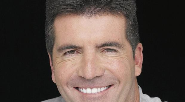 Simon Cowell is amused by a lookalike in a dance troupe