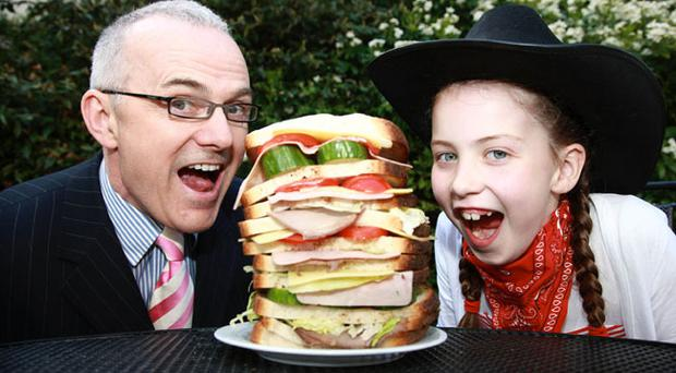 UTV's Frank Mitchell and 8 year old Tierna Murphy enjoying a taste of what's to come at the Irwin's Bakery stand at the Balmoral Show