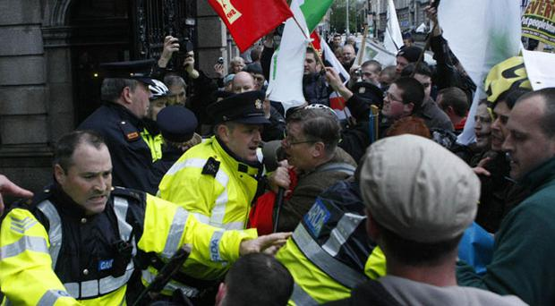 Gardai Clash with protestors marching against government cutbacks outside the Gates of Leinster House in Dublin tonight