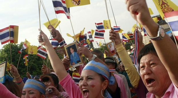 Pro-government supporters wave flags at a rally in Bangkok (AP)