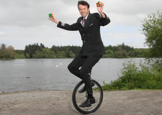 Pilot Adrian Lennon on the unicycle with his Rubik's cubes