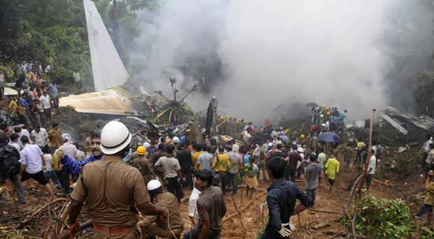 Firefighters perform rescue operations as people crowd around the wreckage of an Air India plane that crashed in Mangalore
