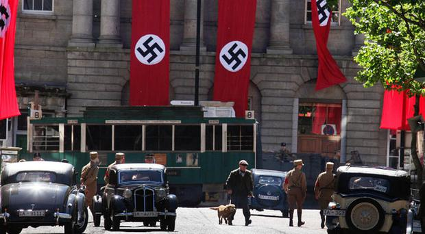 Belfast city centre was transformed into 1930's Berlin yesterday for the making of a new BBC film. Lower Donegall st was closed for most of the day as filming was shot against a sea of swastikas.The film was about writer Christopher Isherwood and the burning of his writings because he was condemmed as a homosexual by the Nazi regime..Belfast is one pof he few European cities where it is not illegal to fly the swatika.pic brendan Murphy.