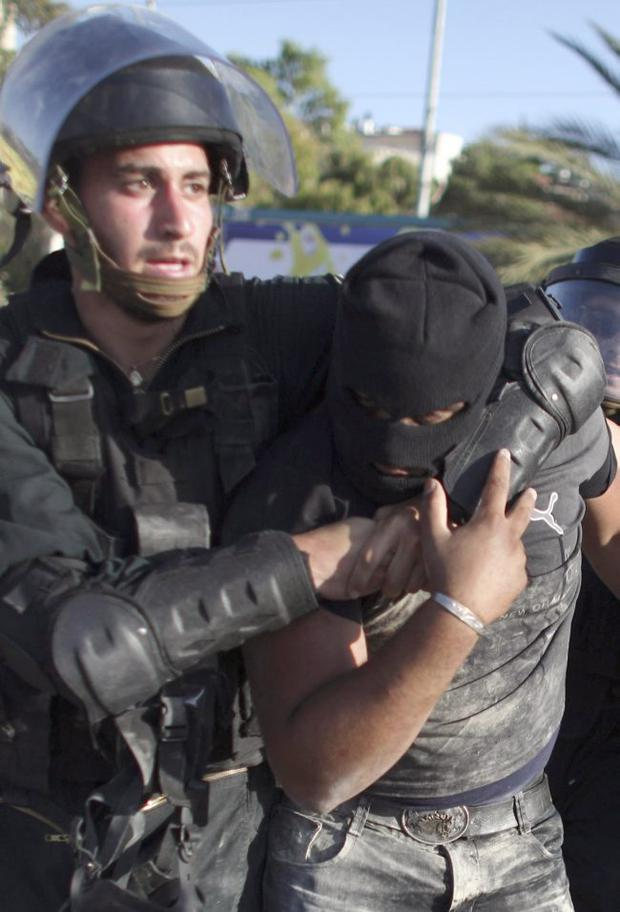 Israeli police detain a masked Arab Israeli protester during clashes in the northern Arab Israeli town of Umm el-Fahm, Monday, May 31, 2010.