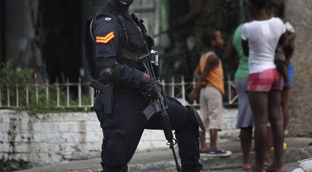 A policemen stands guard at a check point in Tivoli Gardens neighborhood, Kingston