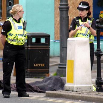 Police stand next to a body covered by a blanket after a shooting in Whitehaven