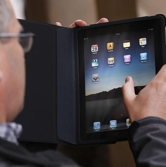 A man uses his new iPad, one of 2010's coolest gadgets, according to a poll