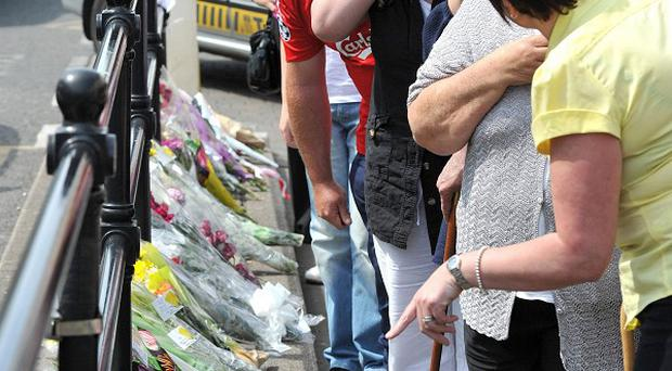 People look at floral tributes that have been left close to the scene where taxi driver Darren Rewcastle was shot in Whitehaven, Cumbria.