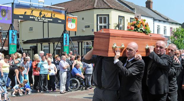Family and friends helping to carry murdered man Bobby Moffett's coffin past the Rex Bar and UVF (Ulster Volunteer Force) memorial murals on the Shankill Road