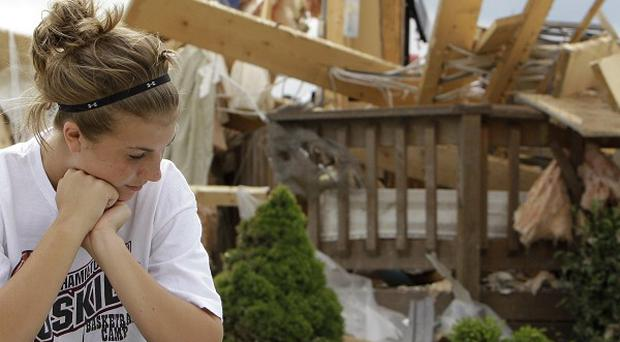 Jordyn Taylor, 13, sits near a neighbour's tornado-ravaged home in Millbury, Ohio (AP)