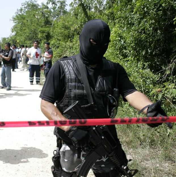 Mexican state police cordon off the area after six bodies were found on the outskirts of Cancun, Mexico. (AP)