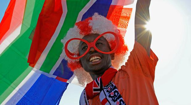 MORULENG, SOUTH AFRICA - JUNE 07: A fan waves flags outside the stadium before the England v Platinum Stars Friendly match at the Moruleng Stadium on June 7, 2010 in Moruleng, South Africa. (Photo by Michael Regan/Getty Images)