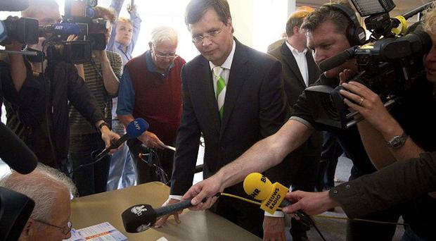 Dutch Prime Minister Jan Peter Balkenende, centre, presents his voter registration card prior to casting his vote in general elections. (AP)