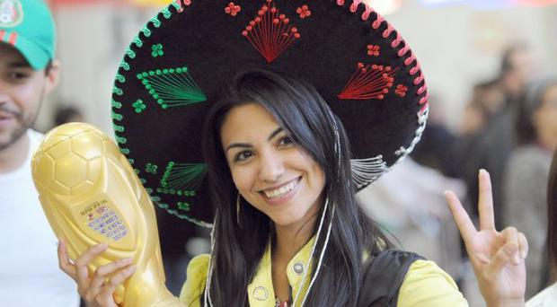 A Mexican fan shows her support in Tambo Airport as fans begin to arrive ahead of the World Cup