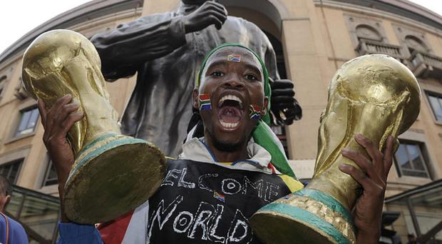 A South African supporter holding copies of the World Cup trophy at Nelson Mandela square in Johannesburg
