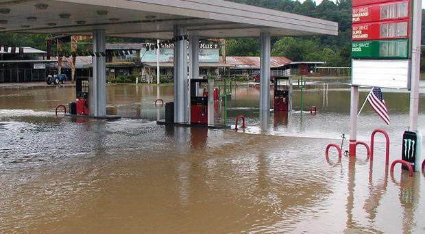 A convenience store flooded by the Caddo River in Arkansas, US, where at least 16 people have died (AP)