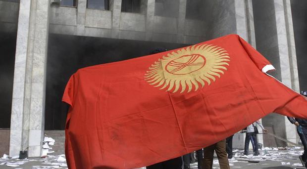 A protester covered by Kyrgyz national flag (AP)