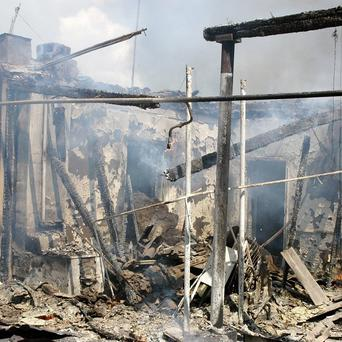 A burned out Uzbeks' residence smolders after being torched by Kyrgyz men in Jalal-Abad, Kyrgyzstan. (AP)