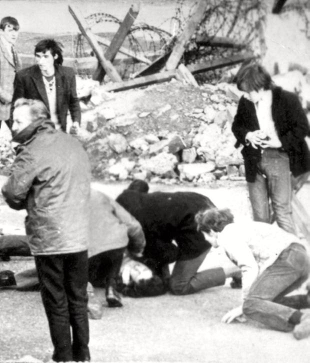 An injured man receiving attention on Bloody Sunday.