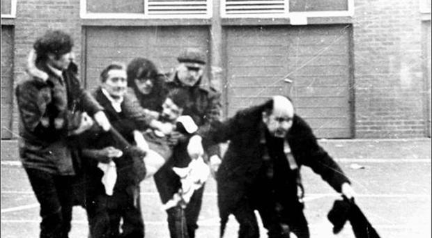 A young Fr Edward Daly (now Bishop Daly) carries a blood-soaked hankie as he leads a group of men trying desperately to carry John 'Jackie' Duddy to safety. Duddy (17) was the first fatality of Bloody Sunday after being shot from behind by paratroopers