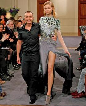Julien Macdonald on the catwalk with a model wearing one of his designs during London Fashion Week last year