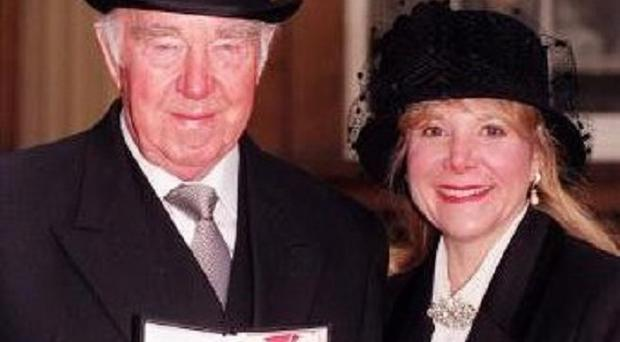 Veteran British film producer and director Ronald Neame, at Buckingham Palace with his wife Dana
