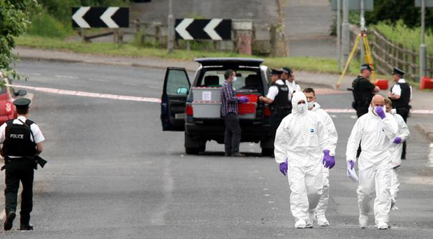 Police and forensic officers prepare to search the area near Aughnacloy police station on Dungannon Road