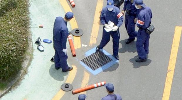 Investigators check a scene at a Mazda plant in Japan where a disgruntled worker drove over people (AP)