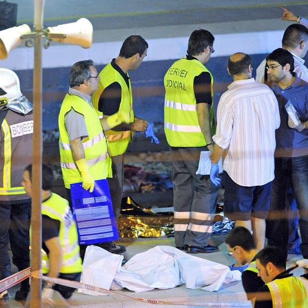 Police and rescue workers inspect the Castelldefels Playa station where a high-speed train struck a group of people
