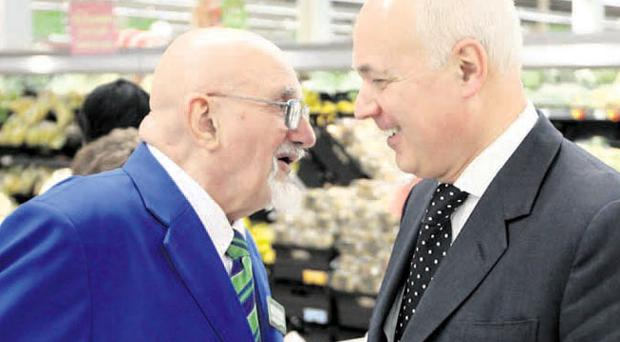 Secretary of State for Work and Pensions Iain Duncan Smith meets 76-year-old Roy Gill, the oldest employee at the Asda store on London's Old Kent Road, during his visit to the shop to meet employees and to discuss working past retirement age
