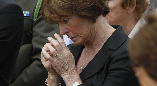 Former Chief of Staff of the Defence Forces, Dermot Earley's wife Mary reacts at his grave side in Newbridge Cemetery after Funeral Mass at St Conleth's Church