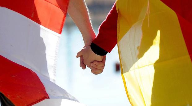 A couple wearing English and German flags hold hands ahead of England's game against Germany