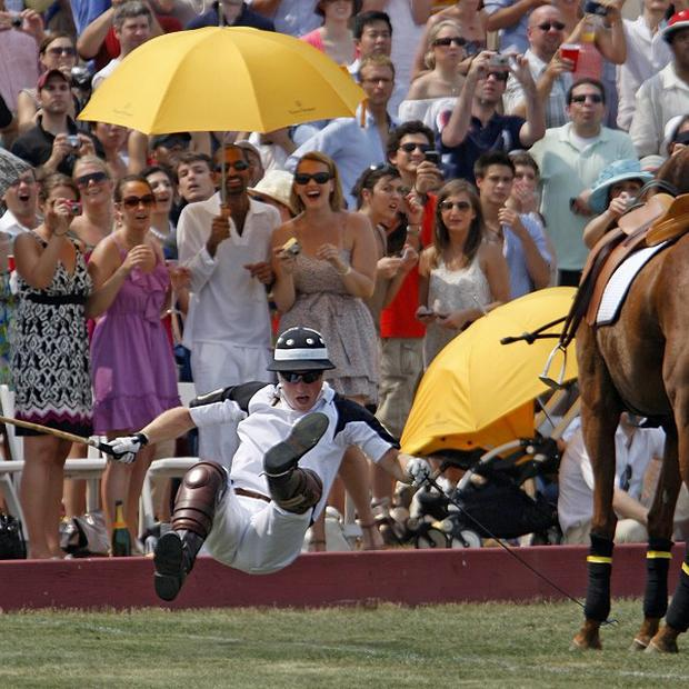 Prince Harry falls off his horse during a polo match in New York (AP)