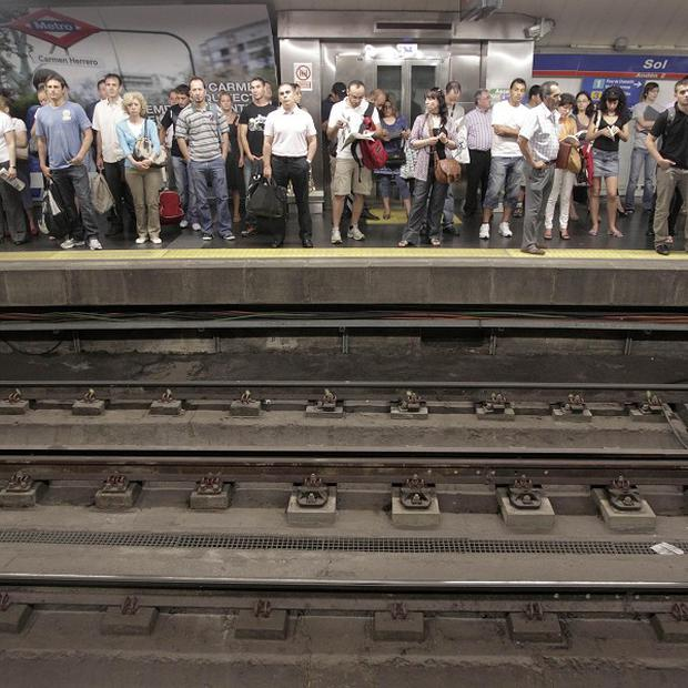Passengers wait on a platform during the subway strike in Madrid